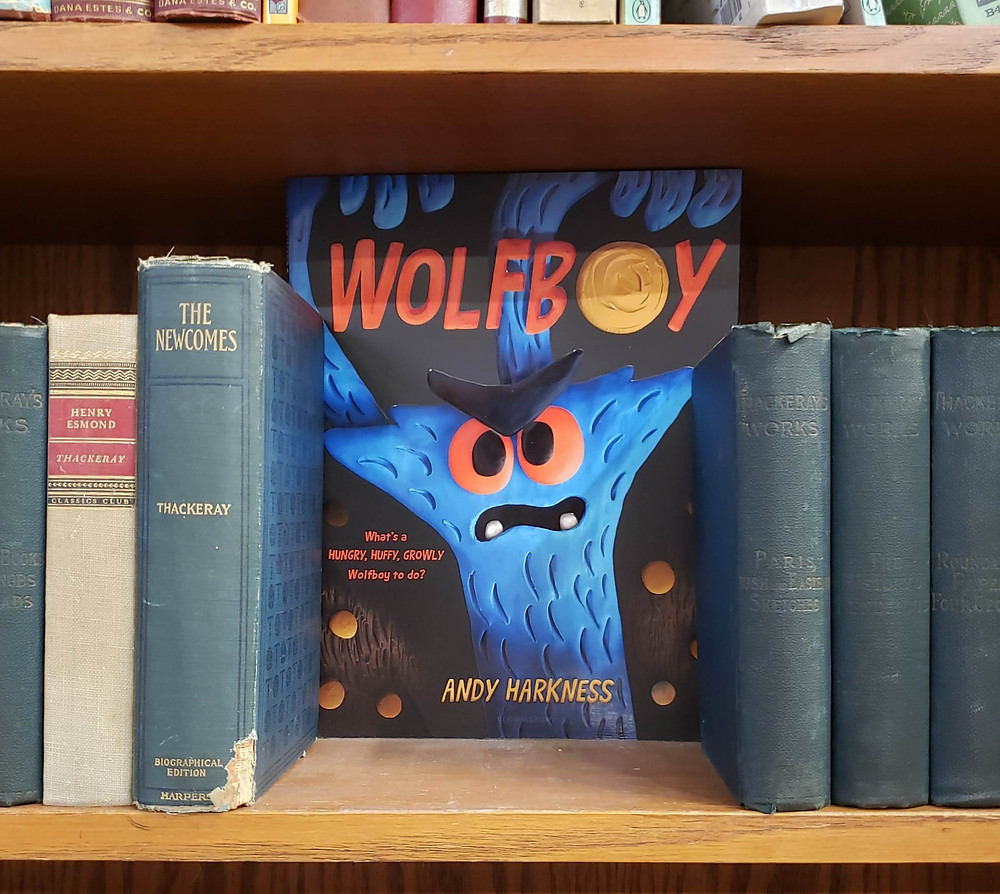 The book Wolfboy by Andy Harkness peers out from in between some antique books on a bookshelf.