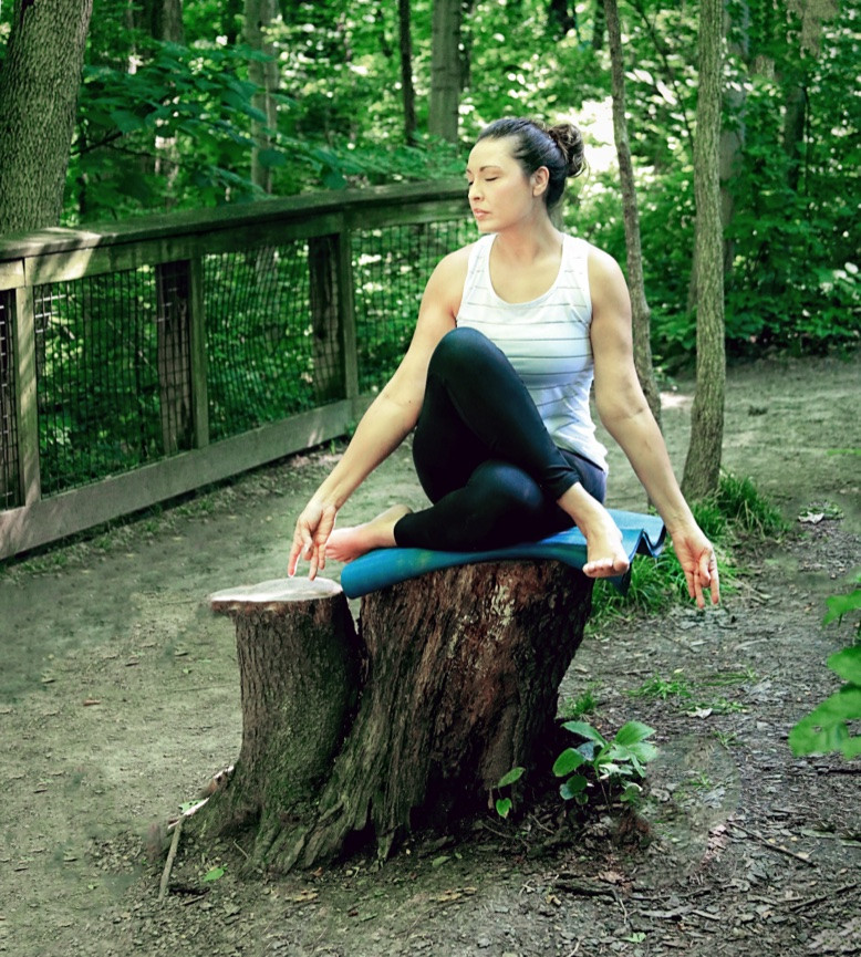 Woman poses in meditation on a tree stump