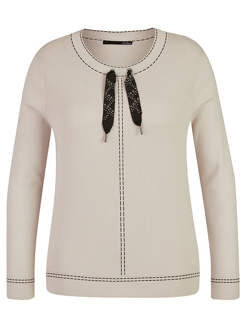 cream sweater top with black stitching