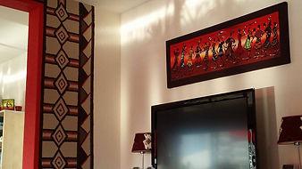 Eén van Lodia's specialiteiten: schilderij met dansende personages van geplakt Afrikaans textiel en acrylverf op doek