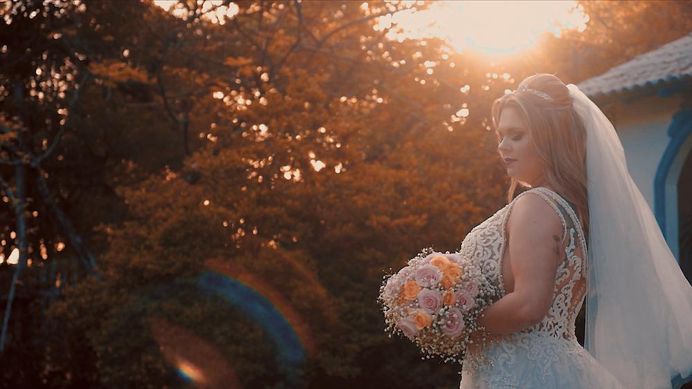 Noiva segurando o buquê no por do sol, casamento ao ar livre