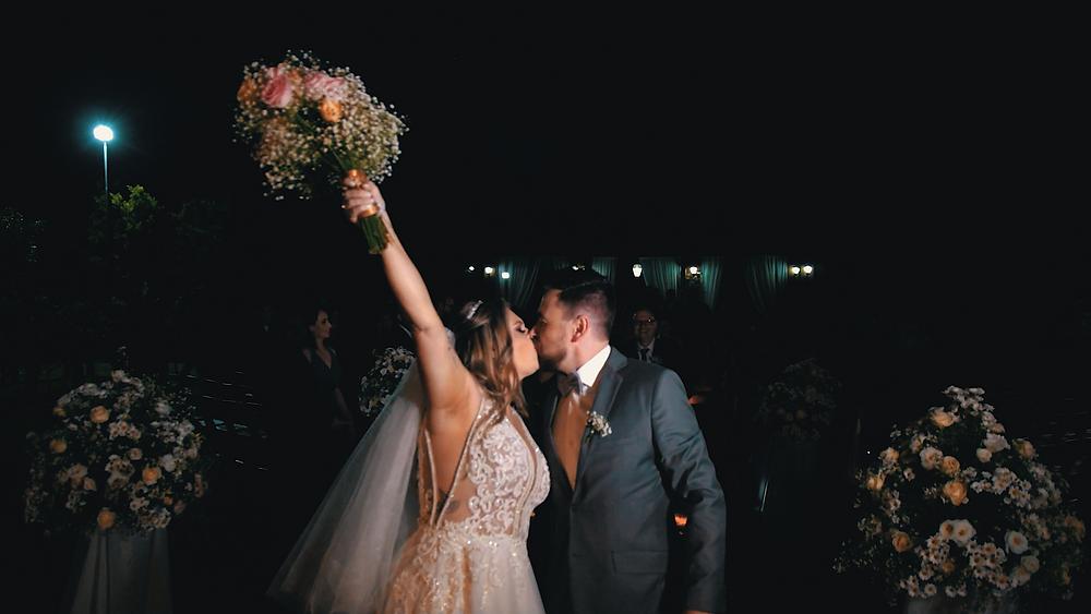 Noivos se beijando depois do casamento, noiva segura buquê