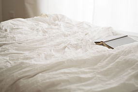 black-and-beige-book-on-white-bed-sheet-