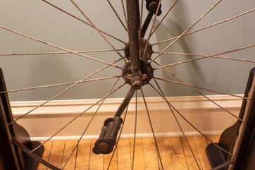 TCHM Exhibit 8.jpg - close-up of front wheel for bicycle (object 89I.605.1). The pedals connect directly to the axle of the front wheel, unlike modern bicycles where they attach at the rear wheel.