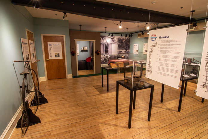 TCHM Exhibit 47.JPG - photograph from inside the WMP exhibit. On the left is a large bicycle next to the wall. In the center of the photograph are several cases and panels, along with a fake cabin and a large black and white mural of two people sitting outside a cabin.