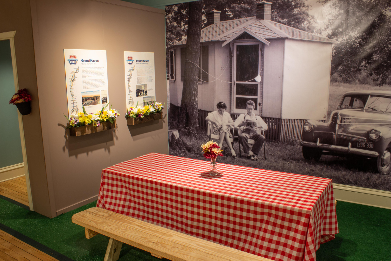 TCHM Exhibit 51.JPG - photograph of the side of the fake cabin and the prop picnic area. On the left side of the photograph is the fake cabin, with two panels mounted on the side and flower boxes hung beneath the panels. In the center is a large wooden picnic table with a red and white checkered tablecloth. Underneath the picnic table is bright green astroturf. Behind the picnic table is a large black and white photo mural of a man and a woman sitting outside a cabin in lawn chairs. Next to them is a vintage car.