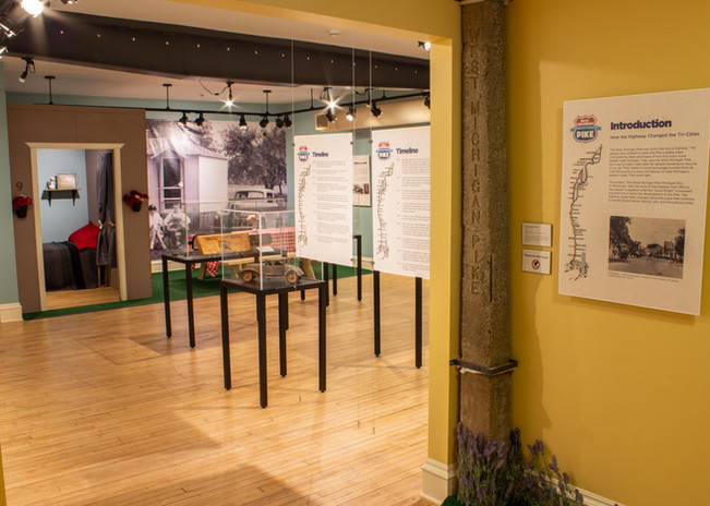 TCHM Exhibit 48.JPG - photograph of the entry to the West Michigan Pike exhibit from the mezzanine. There are several cases with objects in the room and a large cement pillar (the WMP mile marker) with a panel on the right side of the photo.