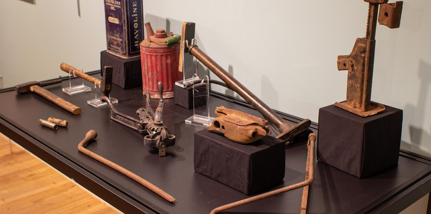 TCHM Exhibit 24.jpg - photograph of twelve objects displayed on the top of a museum case. There are two oil cans, a tire pump, three pieces of a jack, a tire rubber vulcanizer, a tire rim separator, a tire pressure gauge, and two hammers used to change tires. This photograph is from the opposite side of the case as TCHM Exhibit 23.jpg.