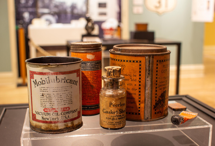 "TCHM Exhibit 20.jpg - photograph of several cans of automotive fluids. There are two in front that are visible in this photograph, shot from the opposite of photograph TCHM Exhibit 19.jpg. The first is 80.9.2, a tin can for containing Mobilubricant brand engine oil (white paper and black letters). The second is a glass bottle with a cork stopper containing Peerless Gasket Shellac. The glass bottle is approximately 4"" tall and 1 ½ to 2"" in diameter."
