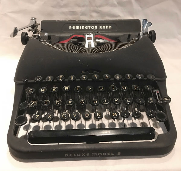 Deluxe Model 5 - photograph of a matte-black typewriter with glossy black keys mounted on black key levers.