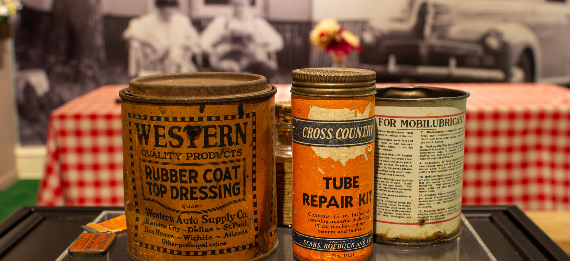 "TCHM Exhibit 19.jpg - photograph of several cans of automotive fluids. There are two in front that are visible in this photograph: 80.9.1 is a tin can for Rubber Coat Top Dressing, with mustard yellow paper and black print around it (approximately 5"" tall) and 80.9.62 is a tin can with a screw cap lid, slightly taller and thinner than 80.9.1 with orange paper and black writing. The contents of 80.9.1 are pieces of a tire tube repair kit."