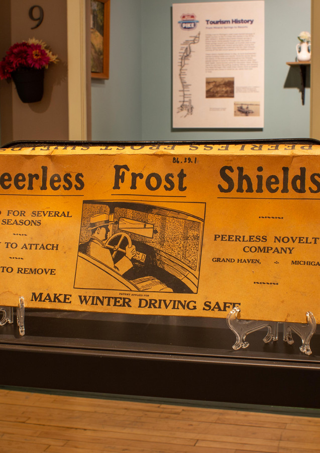 "TCHM Exhibit 9.jpg - yellow cardboard box for a Peerless Frost Shield (object 86.39.1). The box is approximately 9"" high by 24"" wide by 1"" thick. The text on the front of the box reads: ""Peerless Frost Shields. Good for several seasons. Easy to attach. Easy to remove. Make winter driving safe. Peerless Novelty Company. Grand Haven, Michigan."" There is a black and white image of a driver using the frost shield on the front of the box."