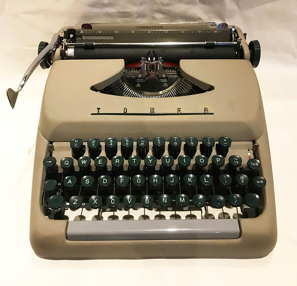 Tower Commander - photograph of a tan typewriter with dark green keys mounted on black key levers.