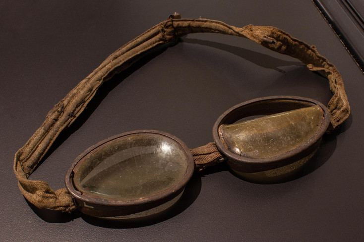 TCHM Exhibit 17.jpg - photograph of a pair of goggles (object 89I.643.1). The goggles have metal eye pieces with plastic lenses which have partially melted. They are connected by a strip of tan string.
