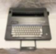 SL 600 Electric - photograph of a medium gray electronic typewriter with white, square-shaped keys. The keyboard resembles more contemporary keyboards.