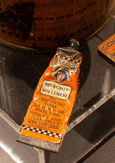 TCHM Exhibit 21.jpg - photograph of an orange paste tube (approximately the same size as travel toothpaste) and a small rectangular orange tin (approximately the same size as a matchbox). The orange tube (object 82.28.60) is Dutch Brand Rim Cement. The orange tin (object 80.9.43) is a set of Valve Insides manufactured by Schrader.