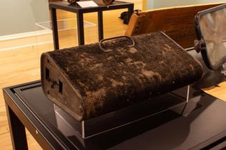 TCHM Exhibit 13.jpg - photograph of the front of a footwarmer (object 80.33.11). This angle shows the carpeted top (where a person would rest their feet to be warmed by the coals inside) and one of the triangular sides of the warmer.