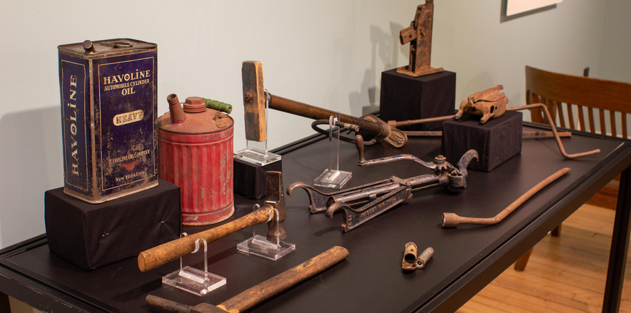 TCHM Exhibit 23.jpg - photograph of eleven objects displayed on the top of a museum case. There are two oil cans, a tire pump, two pieces of a jack, a tire rubber vulcanizer, a tire rim separator, a tire pressure gauge, and two hammers used to change tires.
