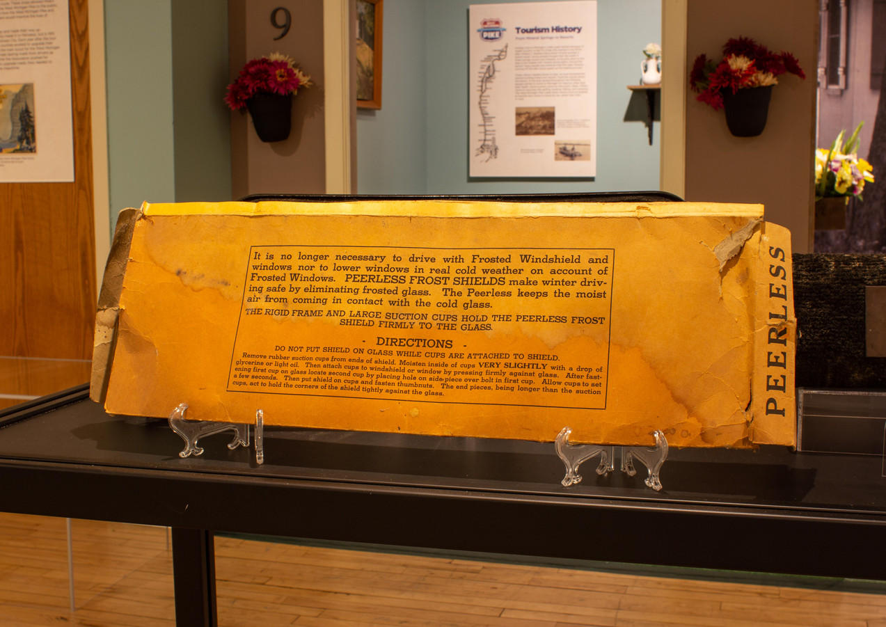 TCHM Exhibit 11.jpg - photograph of the back of a yellow cardboard box for a Peerless Frost Shield (object 86.39.1) at a different angle. The back of the box has text describing the way the product reduces frost on a driver's windshield so it is safer to drive.