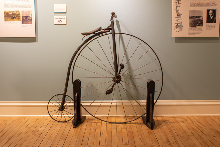 TCHM Exhibit 6.jpg - side view of a metal and wood bicycle (object 89I.605.1). This type of bicycle, called a penny-farthing, has a front wheel that is roughly four times as tall as the rear wheel.