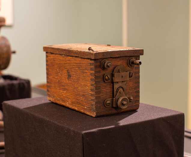 TCHM Exhibit 33.jpg - close-up of a trembler coil (object 89.14.11). The object is a small rectangular box made of wood with copper knobs and bolts projecting from one side.