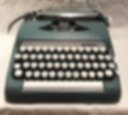 Smith Corona Sterling - photograph of a slate blue typewriter with bright white keys mounted on black key levers