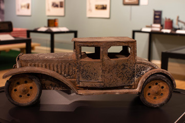 TCHM Exhibit 2.jpg - side view of a metal toy car with significant rust. The car is based on a 1920s coupe style automobile, with a long hood for the engine and a curved trunk (object number 63.35.118).