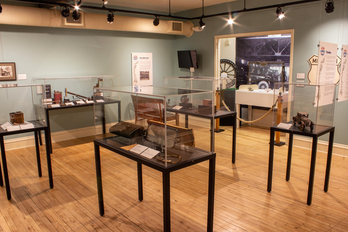 TCHM Exhibit 49.JPG - photograph taken from in front of the fake cabin, looking back towards the entrance to the gallery. There are 5 museum cases in the photograph, each with several objects in them. Behind the cases, there is a large closet display with a Model T windshield and a wheel visible in front of a large black and white photo mural of the inside of a mechanic shop.