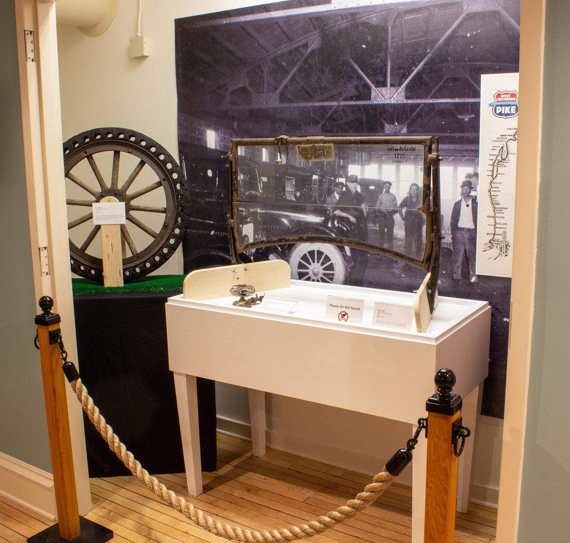 TCHM Exhibit 52.JPG - photograph of the inside of the closet garage scene. In the foreground is a 1925 Model T windshield on a large white pedestal. To the left of the windshield is a large rubber and wooden wheel from a 1920s truck. Behind the windshield and the wheel is a black and white photograph of the inside of a local car garage in the 1920s.