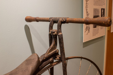 TCHM Exhibit 7.jpg - close-up of handlebars for bicycle (object 89I.605.1). The handlebars are made of a wooden dowel connected to the metal frame in the middle. The front of the leather bicycle seat is also visible.