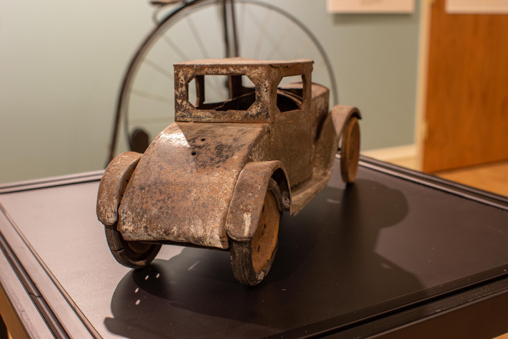 TCHM Exhibit 5.jpg - rear view of a metal toy car (object 63.35.118). The rear of the vehicle is curved downward in a quarter-circle shape to mimic the trunk of a coupe-style car body.
