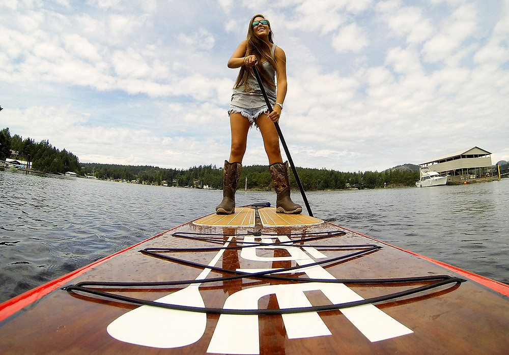Girl paddle boarding though Madeira Park BC