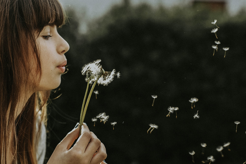 Three-part breathing technique to reduce stress and anxiety.  Girl blowing dandelion