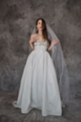 Woman in ballgown with long veil, both by Victoria's Bridal