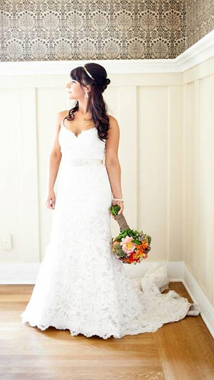Bride in well-fitted white dress with headpiece and floral bouquet