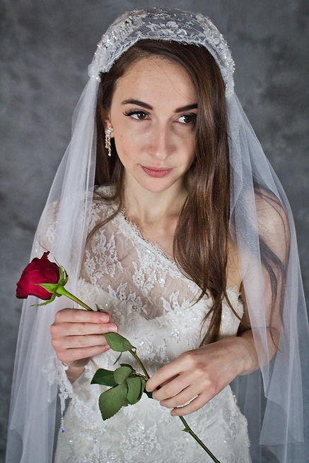 Woman in one shoulder lace wedding gown and matching veil made by Victoria's Bridal with red rose