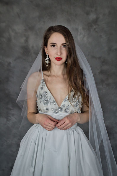Woman with long brown hair in silk ballgown with dramatic earrings and long veil