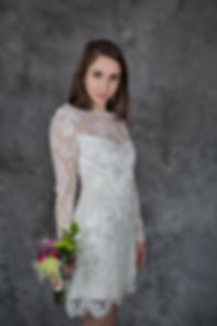 Bride in short cocktail wedding dress in white with lace and bead detail, holding colorful flowers