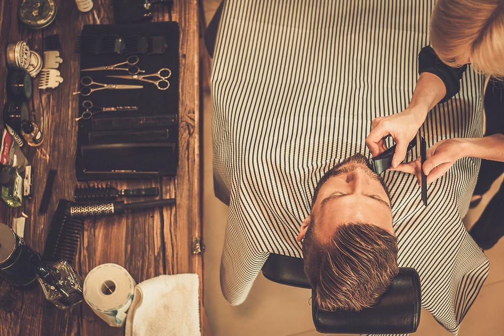 Ein Mann der sich den Bart Schneiden lässt