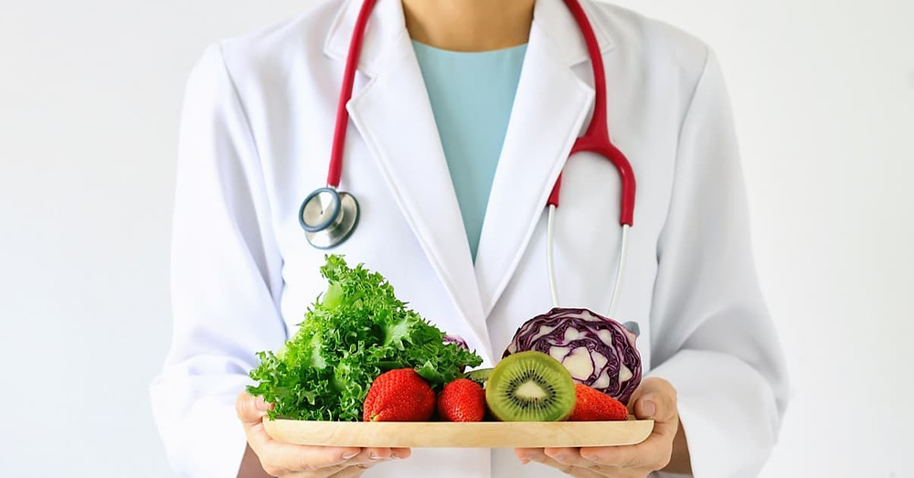 Doctor holing a plate of healthy fruit and veg