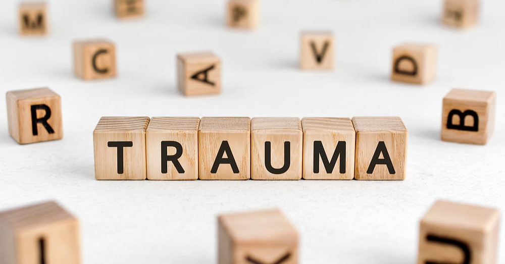 Trauma words from wooden blocks with letters, physical or mental injury trauma concept, white background.