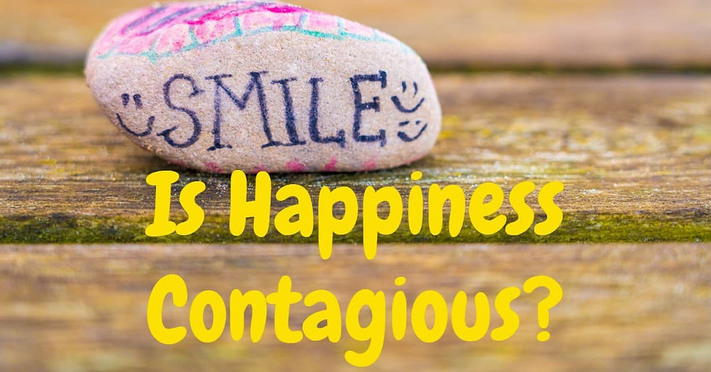 Smile stone on wooden table - Is Happiness Contagious?