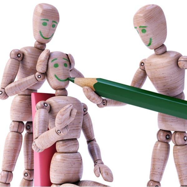 Wooden dolls drawing a happy faces on each other