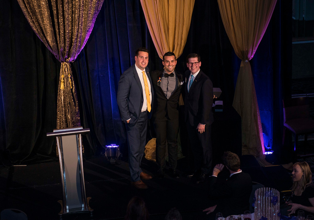 Orlando chapter chairperson, Derek Wood (middle), accepts this year's Member of the Year award.