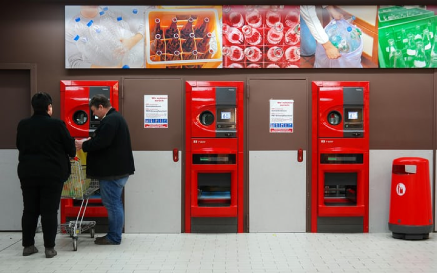 The swedish deposit system in a collecting station with a couple bringing back containers to reuse. No more single use containers. Global Warming. Climate Coping.