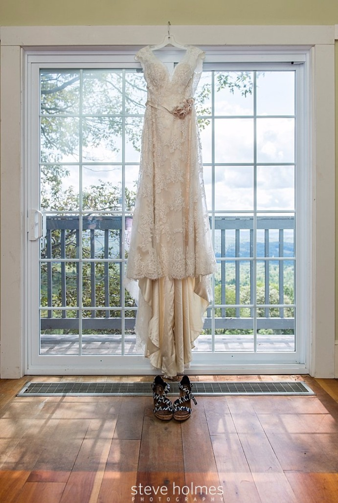 02_Bridal-gown-hangs-in-front-of-window-overlooking-green-mountain-scene_edited