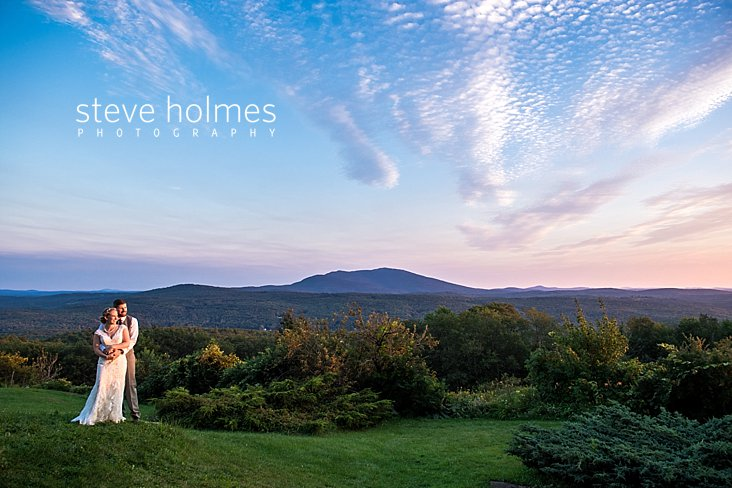 61_Bride-and-groom-stand-on-ridge-line-overlooking-Green-Mountain-range-in-late-summer_