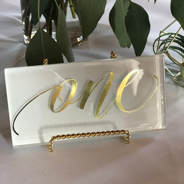 White glass table numbers with gold writing