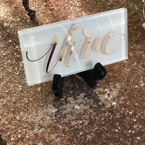 White glass table numbers with rose gold writing