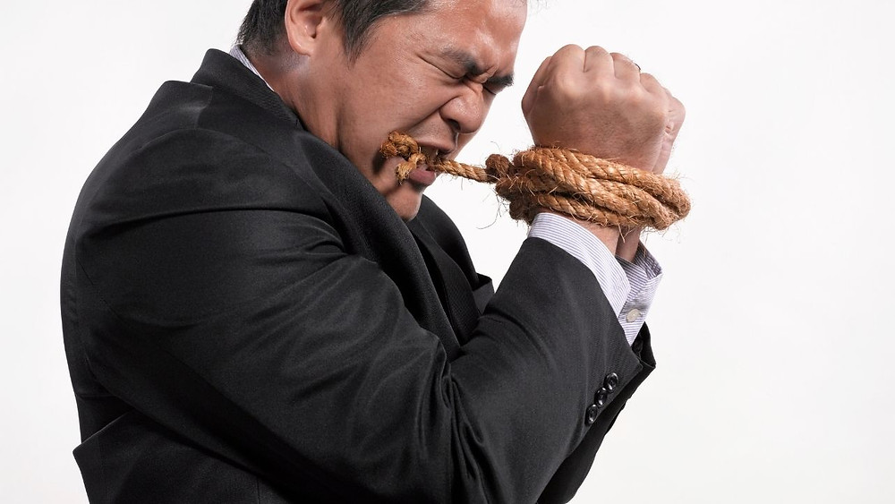 An man in a suit trying to untie his hands from a rope using his teeth.